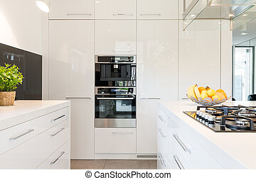 Modern space for cooking - White high-gloss kitchen in...