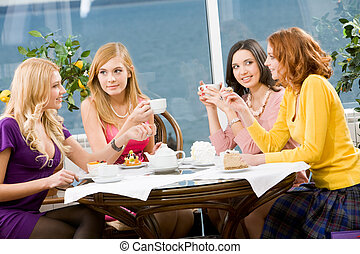 In the cafe - Portrait of four young women sitting at the...