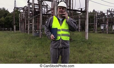 Electrician engineer talking on the phone at substation