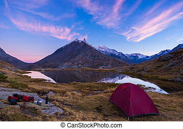 Camping with tent near high altitude lake on the Alps...