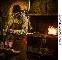 The blacksmith forging the molten metal on the anvil in...