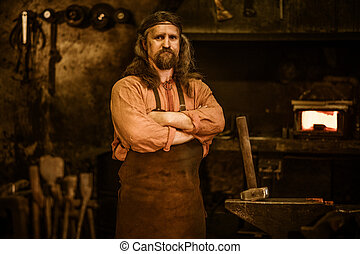Senior blacksmith in smithy - Senior blacksmith standing in...