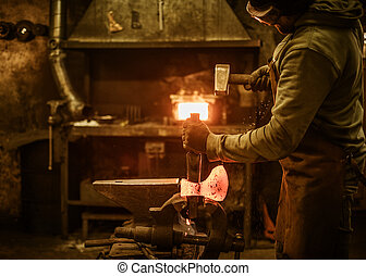The blacksmith forging the molten metal on the rusty vise in...