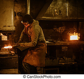 The blacksmith forging the molten metal on the power hammer...