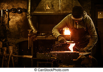 The blacksmith with brush handles the molten metal on the...
