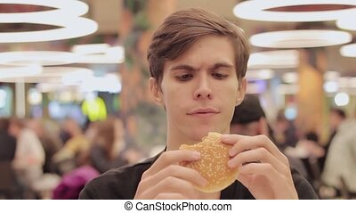 Young men eat hamburger at food court in shopping mall....