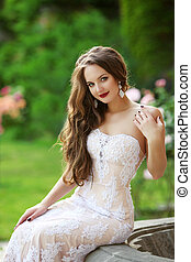 Wedding Portrait Of Beautiful smiling Bride with long wavy hair wearing in white lace wedding dress posing in green park. Romantic. Elegant woman.