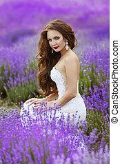 Beautiful brunette bride posing in Lavender Field in the...