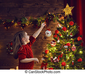girl is decorating the Christmas tree - Merry Christmas!...