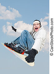 Jumping - Portrait of young boy with snowboard jumping on...