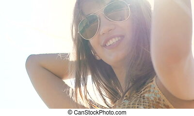 Portrait of pretty female's face smiling on sunny sky background. Slowly