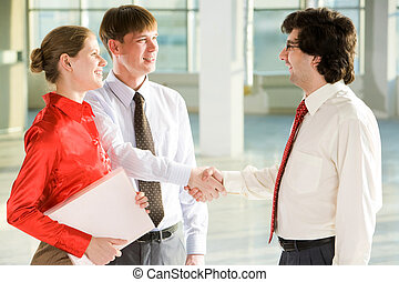 Successful bargain - Business people shaking hands making an...