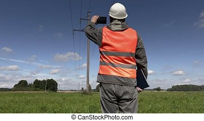 Electrician take pictures under high-voltage lines