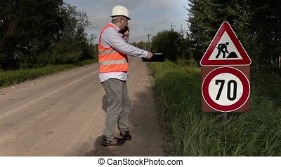 Engineer near to the road signs of road repairing