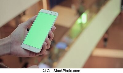 Male hands using smartphone with green screen in shopping mall. Lot of people at the background
