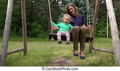 Happy family child girl and mother swinging on park playground.