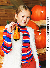 Adorable little girl of 8-9 year old choosing halloween...