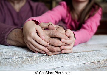 Hands of unrecognizable granddaughter and her grandmother -...