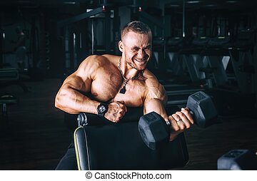 power athletic guy bodybuilder, execute exercise with...