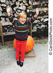 Adorable little boy of 5-6 year old with arms up choosing...