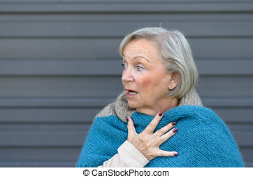 Startled elderly woman clasping her chest in astonishment...