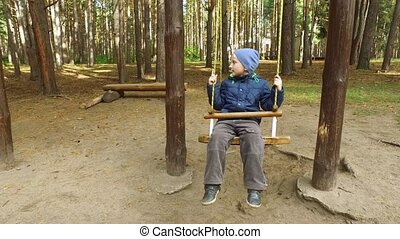 Boy child blonde swinging on a swing. Little boy shows how...