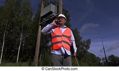 Electrician talking on the phone near high-voltage lines and...