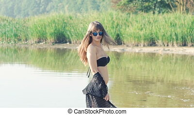 Stylish girl in swimsuit going on the river and posing. Slowly