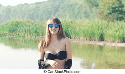 Beautiful girl in swimsuit going on the river and posing. Slowly