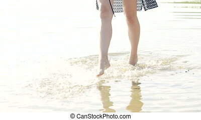 Girl going in the water, undress sunglasses and smiling to camera. Slowly