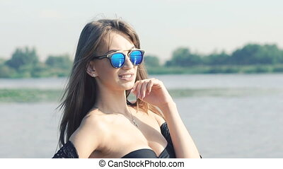Beautiful young girl in swimsuit posing at camera near river. Slowly