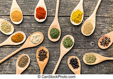 Various spices in wooden spoons. - Various spices in wooden...