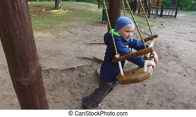 Boy child blonde swinging on a swing. Little boy shows how to swing on the swings. A cloudy fall day
