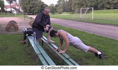 Young athlete do push ups and exercises on stadium