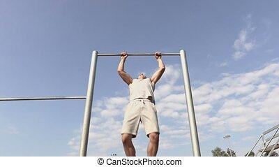 Young athlete rotating, practicing on gymnastic bars