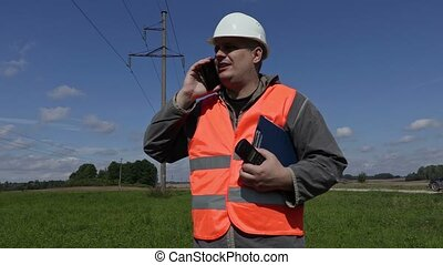 Electrical Engineer talking on smartphone under high-voltage...