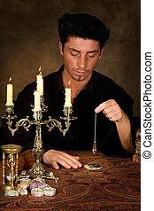 Photo pendulum - Fortune-teller holding a pendulum above a...