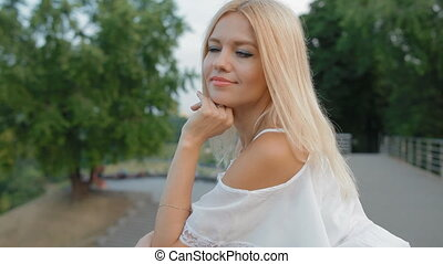 Young blonde woman in light white dress outdoor - Young...