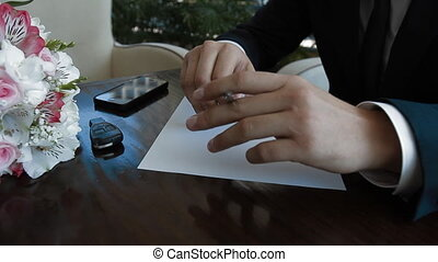 Groom start writing a paper letter to his bride. He can not...