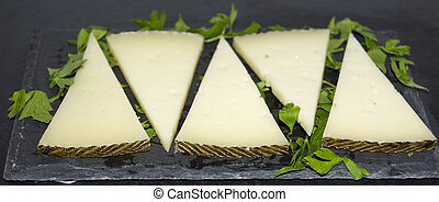 Lots of slices of cheese with parsley on a stone slate -...