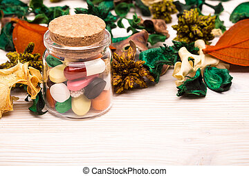 Various pills and capsules with green and orange leaves