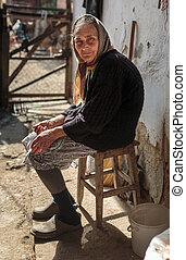 Old farmer woman outdoor - Old woman with kerchief sitting...