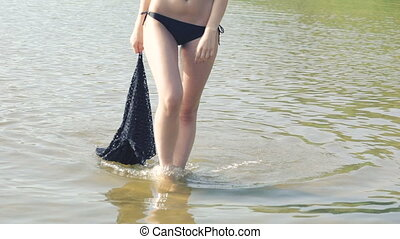 Stylish girl in swimsuit going on the river and putting cloth on water. Slowly