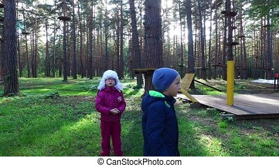 Boy child blond and girl child in glasses walking on green...