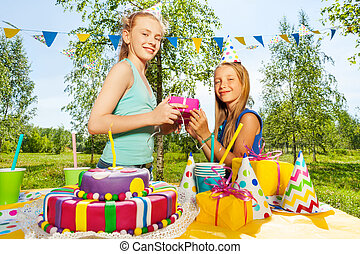 Happy girl giving birthday gift to her friend