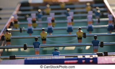 Playing table football outdoor in sunset sun