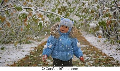 the child looks at the snow falling in the park - the child...
