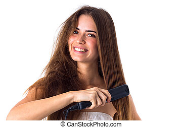 Woman using hair straightener - Happy young woman with long...