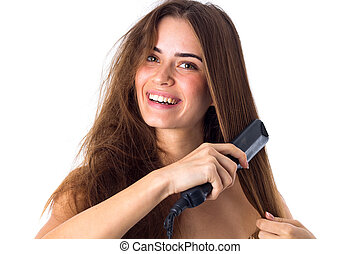 Woman using hair straightener - Charming young woman with...
