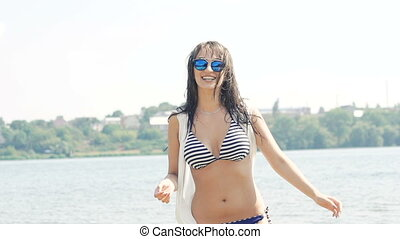 Woman enjoying with waves and drops of water in the river. Slowly
